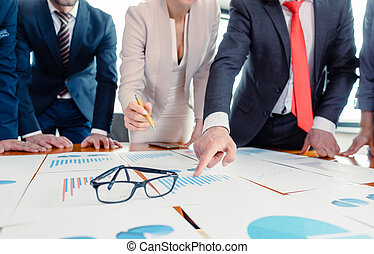 Team of business people analyzing numbers and charts