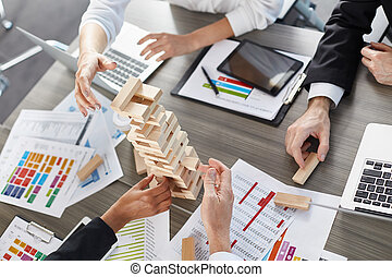 Team of business people build a wooden construction. concept of teamwork and partnership