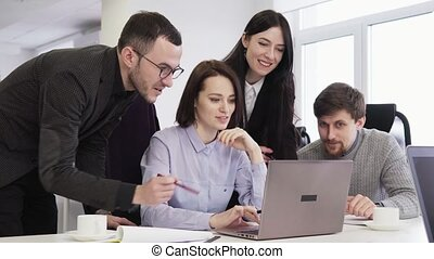 Team of business people looking at laptop screen during creative meeting