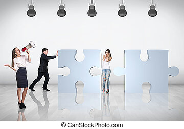 Team of business people try to join puzzle