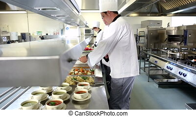 Team of busy chefs working at the order station in a commercial kitchen
