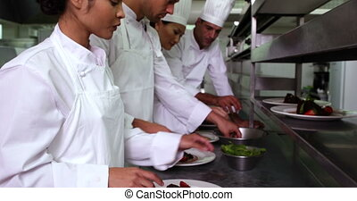 Team of chefs garnishing dessert in a commercial kitchen