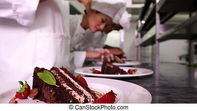 Team of chefs garnishing dessert plates with mint leaves and strawberries in a commercial kitchen