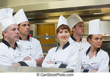 Team of chefs looking away with one smiling at camera