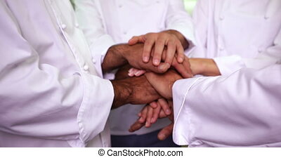 Team of chefs putting hands together and cheering in a...