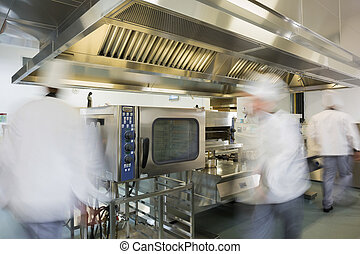 Team of chefs working in a commercial kitchen at a hurried...