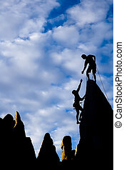 Team of climbers reaching the summit of a rock pinnacle in The Sierra Nevada Mountains, California.
