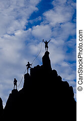 Team of climbers reaching the summit of a rock spire in The Sierra Nevada Mountains.