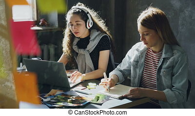 Team of creative designers is working together in light office. Dark-haired lady is listening to music and working with laptop, and blond woman is drawing images in notepad