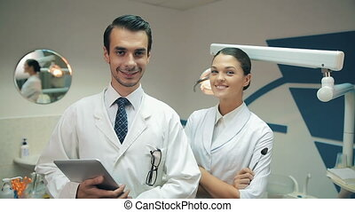 Team of dentists look at camera