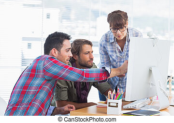 Team of designers working on a computer