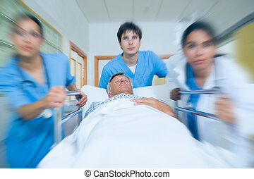 Team of doctor running in a hospital hallway with a patient...