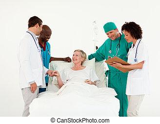 Doctors looking after a patient - Team of Doctors looking...