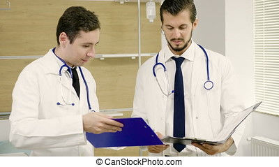 Team of doctors talking in the hospital room with folders in hands