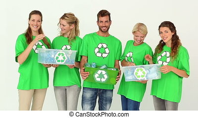 Team of environmental activists smiling at camera holding...