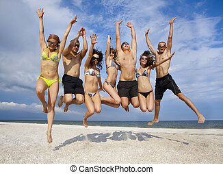 Team of friends jumping at the beach - Joyful team of...