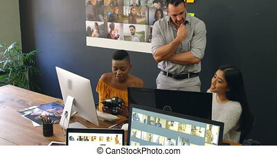 Team of graphic designers discussing over computer at desk 4k