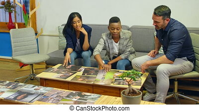Team of graphic designers discussing over photographs 4k