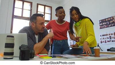 Team of graphic designers discussing over photos 4k