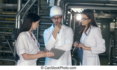 Team of inspectors working at the oil factory