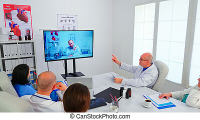 Team of medical staff discussing during video conference