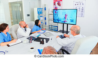 Team of medical staff during video conference with doctor in hospital
