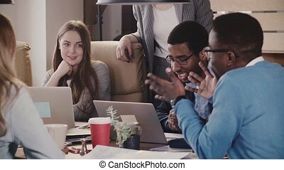 Team of multiethnic freelance workers generating ideas at brainstorming creative session in modern stylish loft office.