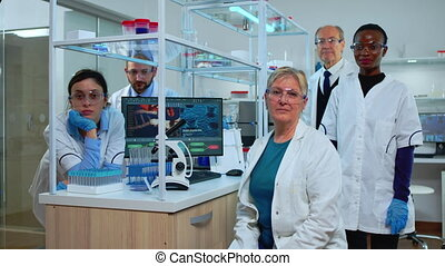 Team of multiethnic scientists sitting in laboratory looking at camera