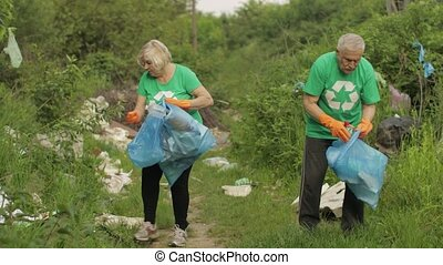 Team of nature activists wearing eco T-shirts picking up plastic garbage cleaning down public park. People save environment. Concept of waste environment, recycle, ecology, pollution and volunteer