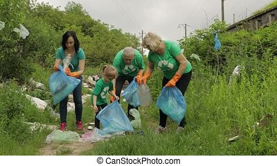 Team of nature activists in eco T-shirts picking up plastic ...