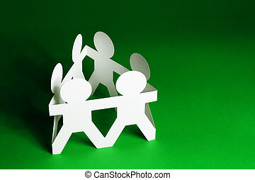 Team of Paper Dolls holding Hands on Green Background