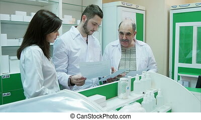 Team of pharmacist checking documents and medicine at drugstore