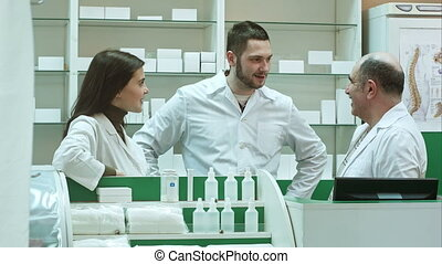Team of pharmacist chemist woman and man standing in pharmacy drugstore and talking positive