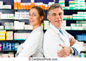 Team of pharmacists in pharmacy - Two Pharmacists standing...