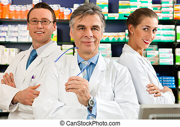 Team of pharmacists in pharmacy - Pharmacist with his team...