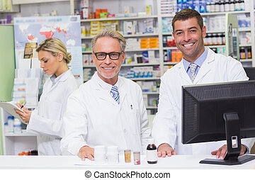 Team of pharmacists smiling at camera at the hospital...