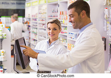 Team of pharmacists using computer at the hospital pharmacy