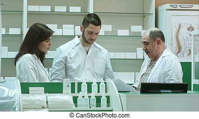 Team of pharmacists working at pharmacy drugstore, senior pharmacist is not satisfied with students job