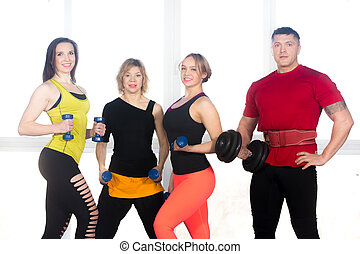 Team of positive sporty people posing with dumbbells in gym