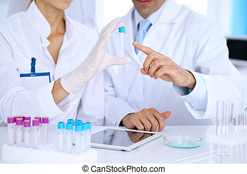 Team of  scientific researchers in laboratory studying substances or blood sample. New vaccine for pharmacology industry is s almost ready. Medicine and science concept