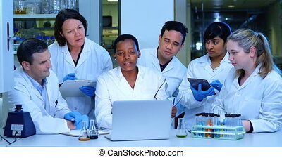 Team of scientist discussing over a laptop 4k