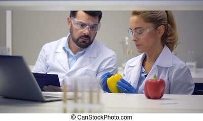 Team of scientist injecting chemicals into peppers in...