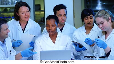 Team of scientists discussing over laptop in laboratory 4k