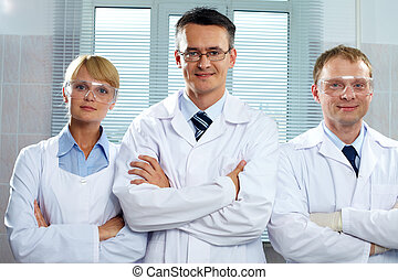 Team of scientists - Three positive scientists looking at ...