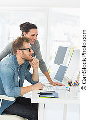 Team of smiling designers looking at the computer