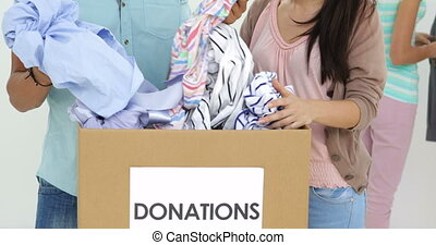Team of smiling workers going through donation box of...