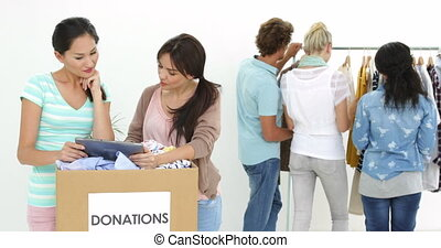 Team of smiling workers using tablet beside donation box in...