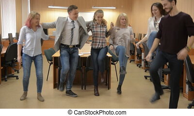 Team of successful people dances a cancan in the computer room