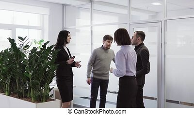 Team of successful people talking and shaking hands after business meeting