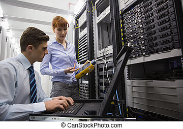 Team of technicians using digital cable analyser on servers ...
